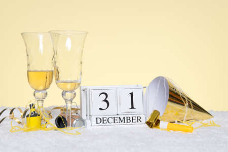 New Year party still life with two empty glasses of Champagne and a date block showing 31st December with streamers. Copy space on the background for your own message such as invitation.