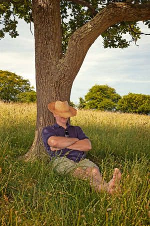 A man taking an afternoon nap in the shade of an old tree on a hot sunny summers day.