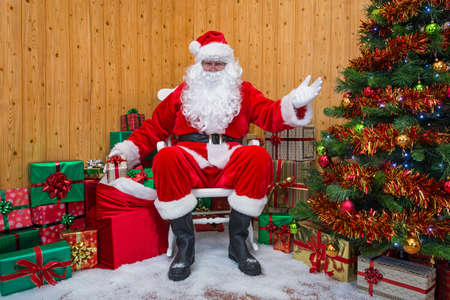 Santa Claus getting a gift wrapped present out of his sack as he welcomes you into his grotto.