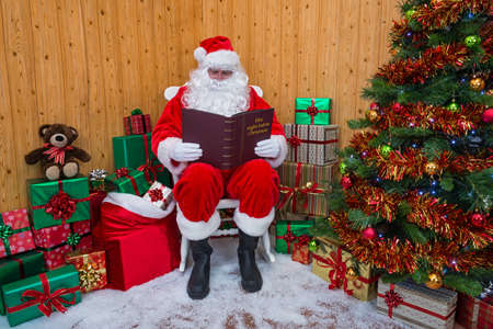 Santa Claus sitting in his grotto surrounded by a tree with presents and gift wrapped boxes whilst he reads his favourite book - The night before Christmas  Standard-Bild