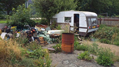 An old derelict abandoned caravan and motorbike plus other bits of rubbish on a piece of overgrown land.