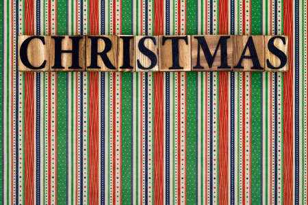 The word Christmas made from wooden block letters on a colourful striped background.
