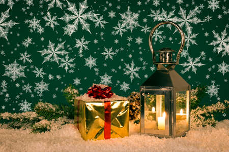 Christmas lantern still life with a gift wrapped present and snowflakes.