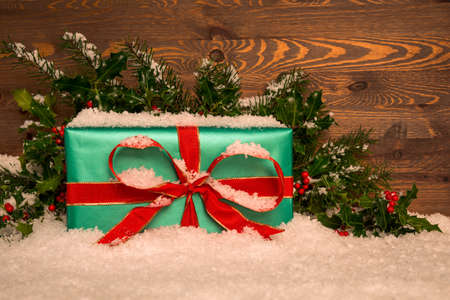 Christmas present gift wrapped in green paper with red ribbon with holly and snow against a wooden background, copy space for your own message. Standard-Bild