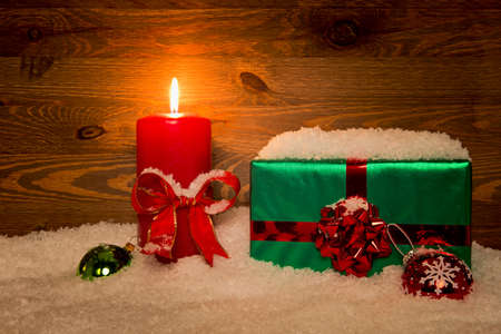 A gift wrapped Christmas present with candle and snow against a wooden background.