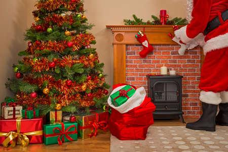サンタ クロースのプレゼントの包みを提供は、ツリーの下にクリスマス ・ イヴにおもちゃでいっぱいの袋を良い女の子と男の子。