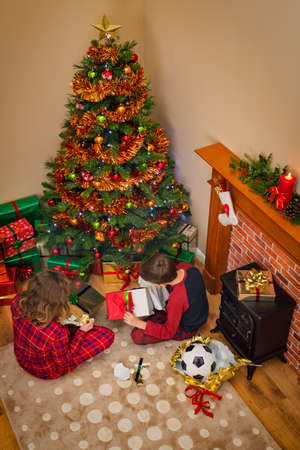 Overhead view of Children opening their gift wrapped presents on Christmas morning sitting next to the tree and fireplace.