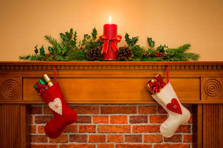 Two Christmas stockings with gift wrapped presents hanging on a mantelpiece over a fireplace, plus burning candle with festive garland including holly, fir and pine cones.