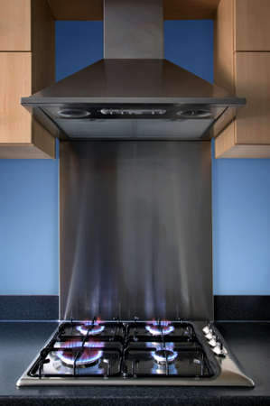 Modern steel kitchen gas hob and extractor hood.