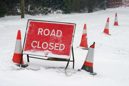 A red Road Closed sign and traffic cones covered in fresh fallen snow on a lane in Hampshire, England. Taken on 2nd March 2018. Standard-Bild