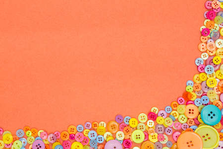 Lots of colourful buttons on an orange textured paper background with blank copy space. Standard-Bild