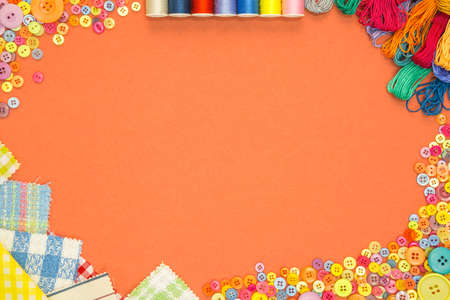 Arts and Crafts background with material and buttons on an orange textured paper background with blank copy space. Standard-Bild