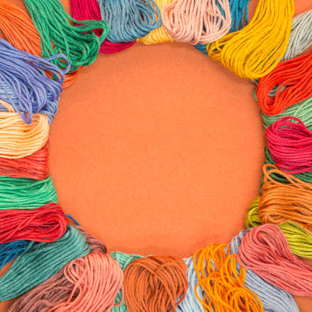 Lots of knitting wool samples on an orange textured paper background with copy space in the middle. Standard-Bild