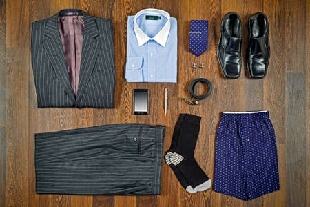 A flat lay arrangement of mens business attire with grey pin striped suit, white collar shirt, black shoes and matching accessories. Standard-Bild