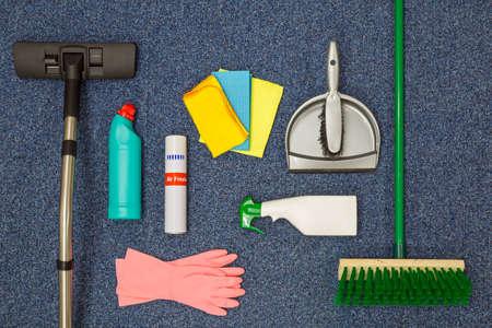 A flat lay arrangement of cleaning equipment on a blue office carpat background. Standard-Bild