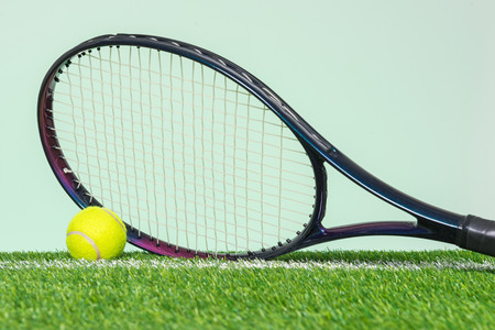 A tennis racket and ball on grass with plain green background.