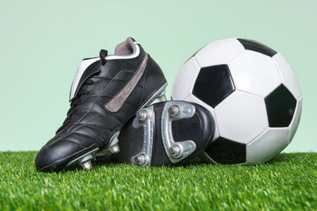 Football or Soccer boots and ball on grass with green background. Standard-Bild