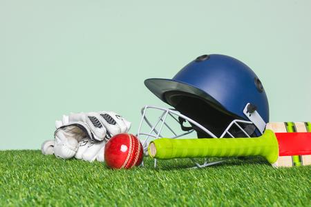 Kricketausrüstung mit Schläger, Ball, Helm und Handschuhen auf Gras mit grünem Hintergrund.