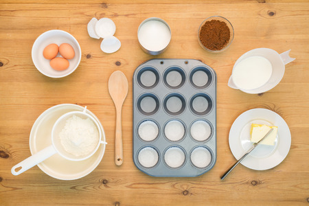 Overhead flat lay arrangement of Cup Cake making ingredients and equipment on a kitchen table. Standard-Bild