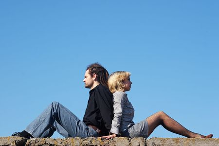 couple sitting back to back Stock Photo