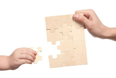 mens and childs hands finishing set of puzzles