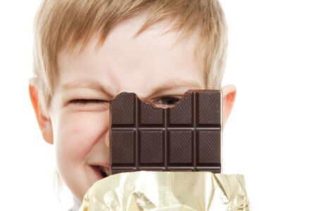 smiling boy looking through bar of chocolate Stock Photo