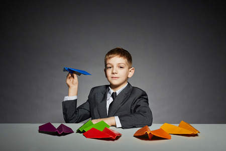 Boy in  suit launching blue paper plane photo