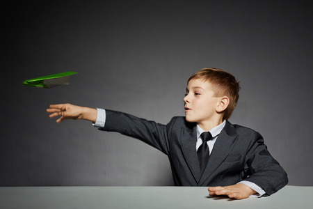 Boy in  suit launching green paper plane photo