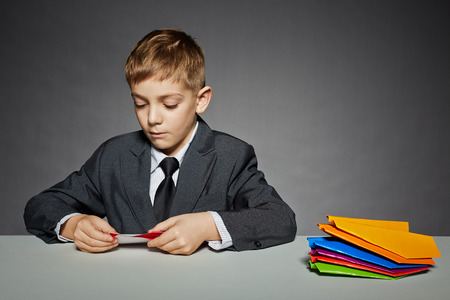 Boy in suit making color paper planes photo