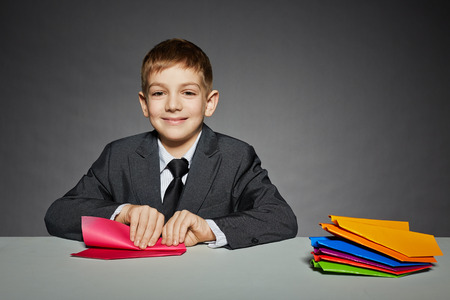 Boy in suit making red paper plane photo