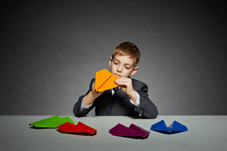 Boy in suit making yellow paper plane photo