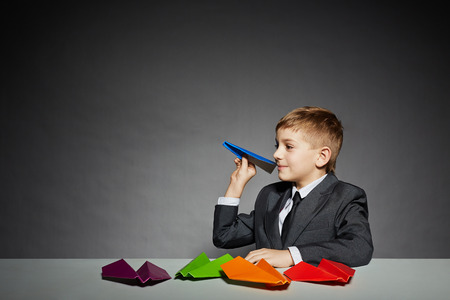Boy in  suit about to launch color paper plane photo