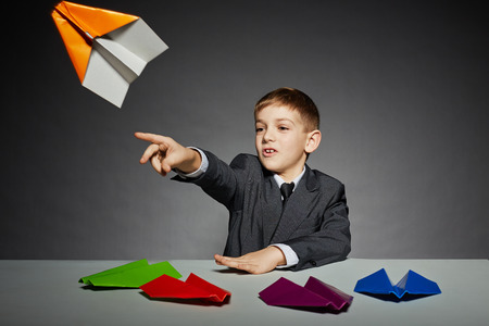 Boy in business suit launching color paper plane photo