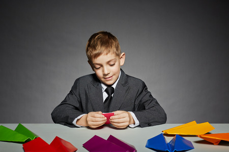 Boy in business suit making color paper planes photo