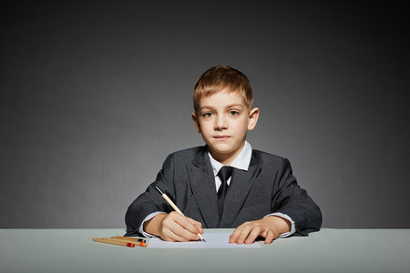 Boy in suit writing photo
