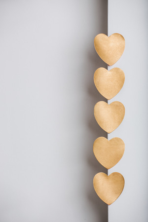 gold textured background: Gold heart stickers on grey textured background with blank space Stock Photo