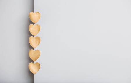 gold textured background: Gold hearts on grey textured background with blank space Stock Photo