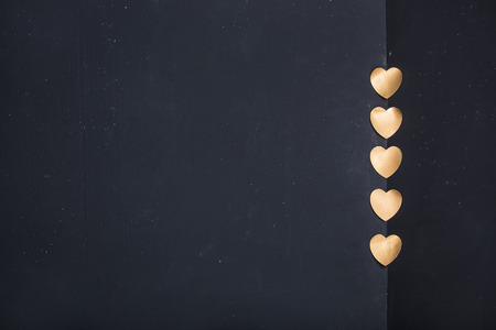 Gold heart stickers on dark texture background with blank space photo