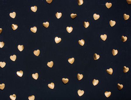 gold textured background: Gold heart stickers on dark textured background Stock Photo