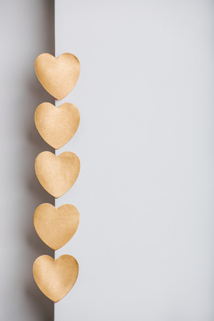 gold textured background: Gold heart stickers on grey textured background