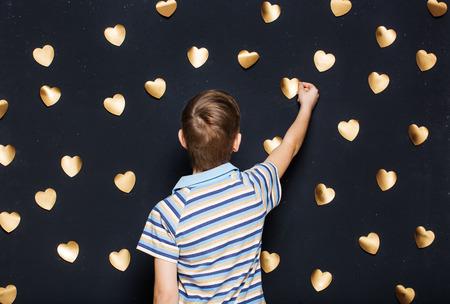 attaching: Boy attaching hearts on dark background