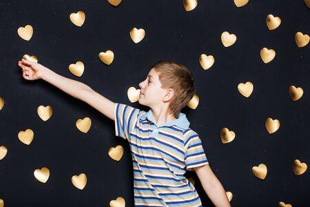 attaching: Boy attaching hearts on dark textured background