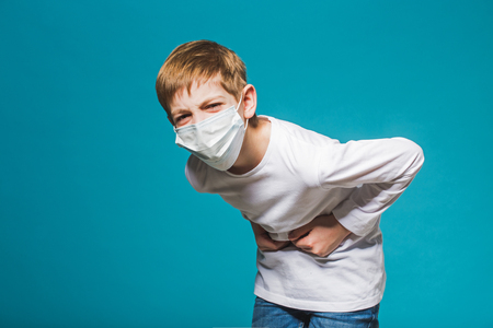 stomach ache: Boy wearing protection mask having stomach ache Stock Photo