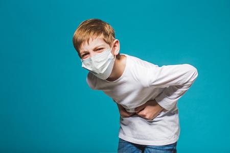 dolor de estomago: Muchacho que desgasta la máscara de protección que tiene dolor de estómago