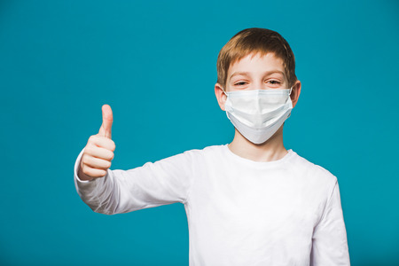 sick child: Boy showing thumb up in protection mask Stock Photo