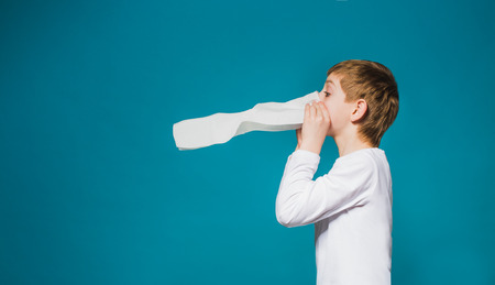 Boy in white clothes blowing his nose photo