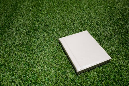 cover concept: White leather book lying on the grass