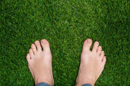 pies masculinos: Pies para hombre de pie sobre la hierba close up