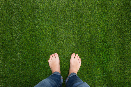 Mens Füße stehen auf dem Gras