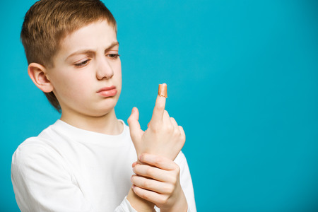 child finger: Unhappy boy in white clothes with adhesive plaster on his finger Stock Photo